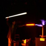 Robert  replicating one of Tesla's experiments. Robert is holding two flourescent tubes which are being lit wirelessly by the Tesla Coil. Thousands of volts are passing via the orange tube through Robert's body into the second (white) tube. The coil is electrically tuned at high frequencies, allowing the current to pass through Robert's body without harm.